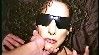 Perverted flatchested black-haired in sunglasses lies back so dude can fuck her mouth